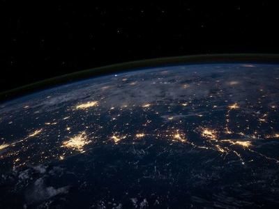 Photograph of the earth with lights on at night.