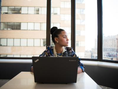 A woman using a laptop peers out a window.