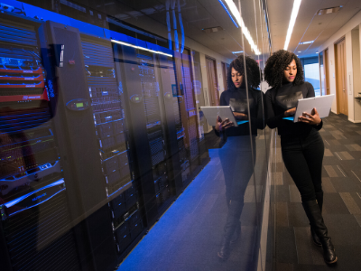 A women holding a laptop stands next to a stack of servers.